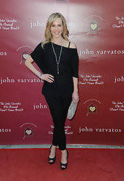 Julie looked stylish at the Stuart House Benefit in an off-the-shoulder black sweater and matching pants.