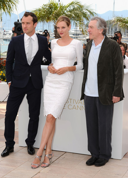 Uma Thurman added shine to her white ladylike dress with strappy silver sandals.