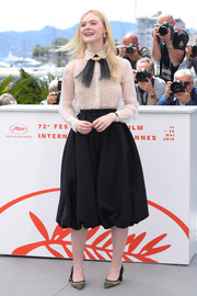 Elle Fanning attended the 2019 Cannes Film Festival jury photocall wearing a sheer, embroidered white blouse by Dior Couture.