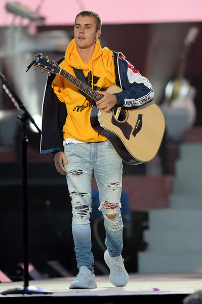 Justin Bieber Ripped Jeans [handout,one love manchester,string instrument,musician,guitarist,guitar,performance,music,yellow,musical instrument,music artist,benefit concert,justin bieber,sales,use,stage,manchester,england,love manchester benefit concert]