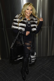 Lil Kim arrived for the Kanye West Yeezy Season 3 fashion show wearing a fur-trimmed coat over a mesh-panel catsuit.