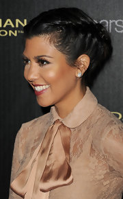 Kourtney Kardashian donned a lacy blouse paired with a blush-colored skirt for the launch of the Kardashian Kollection. She punctuated her whimsical look with a braided updo.