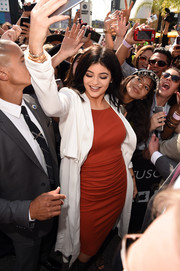 Kylie Jenner arrived for the Kendall + Kylie fashion line launch wearing a white duster coat over a red dress, both by Topshop.