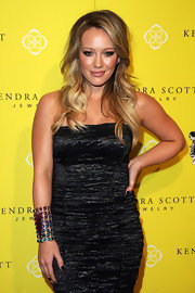 A glowing and bronzed Hilary Duff donned a metallic frock for the Kendra Scott jewelry bash. She finished off the look with full lashes and loose curls.