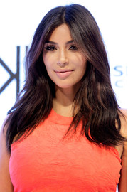Kim Kardashian sported her signature center part with subtly wavy layers during the Kardashian Kollection spring launch in Sydney.