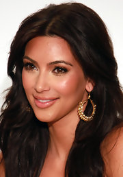 Kim Kardashian paired her long tresses with gold hoop earrings that were encrusted with gemstones.