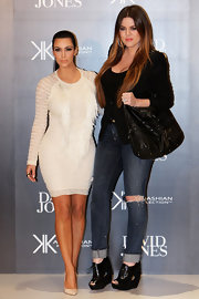 Khloe topped off her distressed jeans and black blazer combo with black wedges lace-up booties.