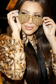 While doing a little shopping, Kim was caught trying on a cool pair of chain aviator shades.