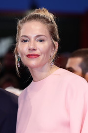 Sienna Miller styled her hair into a classic bun for the Venice Film Festival Kineo Prize.