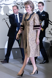 Queen Mathilde of Belgium looked classy in a printed gold coat with purple velvet trim at the the 'Van Eyck: An Optical Revolution' exhibition.