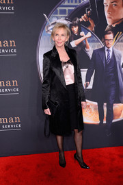 Trudie Styler went for simple elegance in a black satin coat layered over a silk cami and a pencil skirt at the 'Kingsman: The Secret Service' premiere.