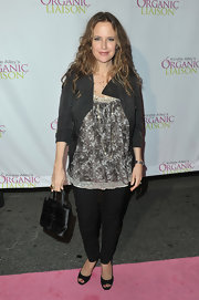 Kelly Preston carried a petite black satin evening bag to the Organic Liaison store opening.