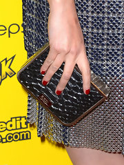 Roxane Mesquida accessorized her metallic dress with more hardware with this hard case clutch.