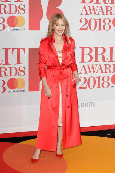 Kylie Minogue Trenchcoat [clothing,carpet,red,red carpet,premiere,flooring,fashion,pink,outerwear,event,red carpet arrivals,kylie minogue,brit awards,relation,the o2 arena,england,london]