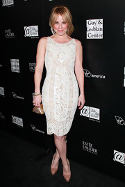 Emma paired her intricate white frock with nude patent leather pumps with ankle-strap detailing.