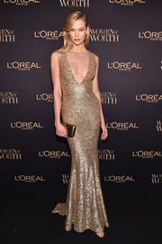 Karlie Kloss amped up the shine with a gold clutch.