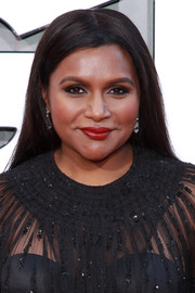 Mindy Kaling gave her dark outfit a pop of color with a swipe of red lipstick.