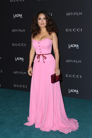 Salma Hayek added an extra pop of feminine color with a burgundy plexi clutch, also by Gucci.