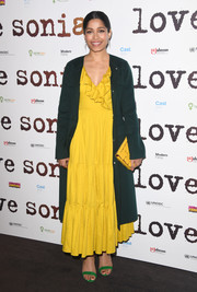 Freida Pinto arrived for the UK premiere of 'Love Sonia' wearing a forest-green wool coat over a yellow ruffle dress.