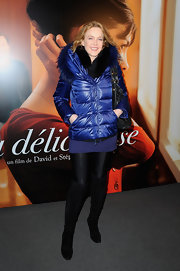 Agnes Soral opted for a futuristic winter look in a blue puff jacket with metallic sleeves and a fur-trimmed hood.