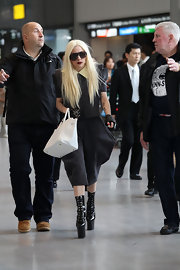 Lady Gaga carefully walked through the airport in a pair of dangerously high patent leather platform boots.