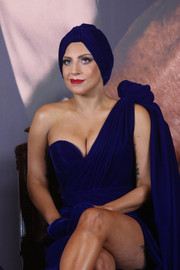 Lady Gaga channeled Old Hollywood with this cobalt turban and one-shoulder gown combo for a press conference in Brussels.