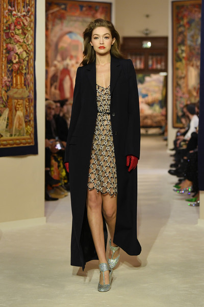 Gigi Hadid layered a long black coat over an embellished dress for her walk on the Lanvin runway.