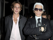 Karl wears a black leather pair of gloves, in signature fashion.