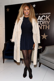 Laverne Cox visited Macy's Herald Square wearing a cream fur coat over a navy mini dress.