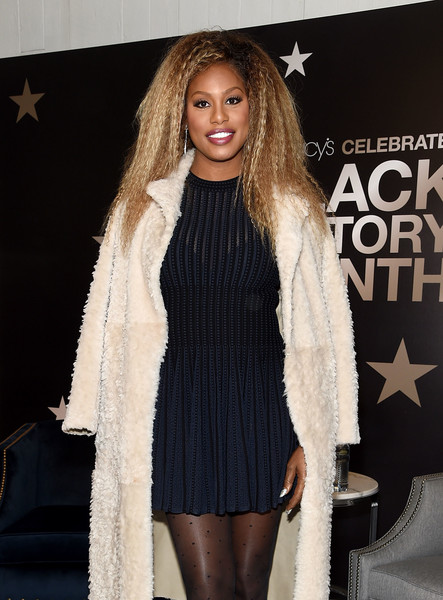 Laverne Cox layered a pleated navy mini dress under a fur coat for her visit to Macy's Herald Square.