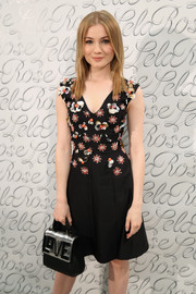Skyler Samuels accessorized with a cute black and silver 'Love' purse at the Lela Rose fashion show.