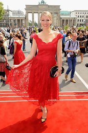 Ruth Moschner chose a bright red lace dress for her look at the Lena Hoschek runway show in Berlin.