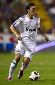 Mesut Ozil controls the ball while wearing his Real Madrid kit.