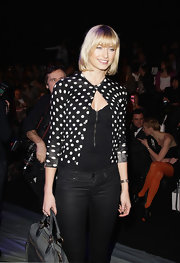 Lena plays with contrast in a polka-dot cardigan over a zip-up corset during fashion week in Germany.