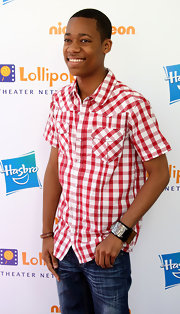 Tyler pulls off this super casual red plaid shirt by matching it with his leather cuff and bracelet.