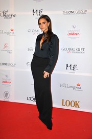 Victoria Beckham kept it sleek and elegant in a black silk blouse with a keyhole neckline when she attended the London Global Gift Gala.