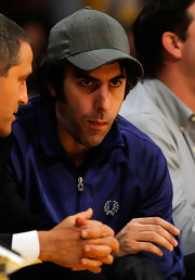 Sacha Baron Cohen sat court side at the Los Angeles Clippers game wearing a plaid baseball cap.