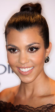 Kourtney completed her fluttering lashes and sleek bun with nude lipstick.