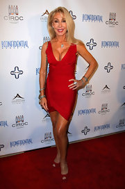 Linda Thompson rocked some major va-va-voom cleavage in a red bandage dress with an asymmetrical hem.