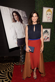 Neve Campbell dressed up her simple top with a color-block step-hem skirt.