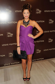 Erin carries a black leather clutch with her vibrant cocktail dress for the Louis Vuitton collection launch.