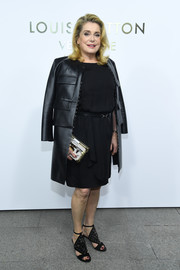 Catherine Deneuve punctuated her black look with a silver box clutch by Louis Vuitton.
