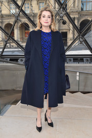 Catherine Deneuve arrived for the Louis Vuitton fashion show wearing a loose navy wool coat over an electric-blue lace dress.