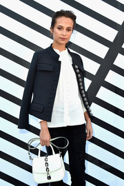 Alicia Vikander arrived for the Louis Vuitton fashion show carrying a chain-embellished white satchel from the brand.