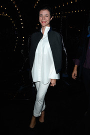 Garance Dore attended the Louis Vuitton fashion show wearing white jeans, a loose blouse, and a black zip-up jacket.