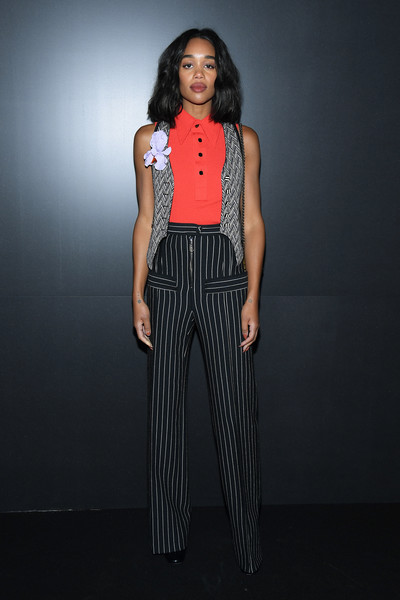 Laura Harrier layered a gray herringbone vest over a red top, both by Louis Vuitton, for the brand's Fall 2020 show.