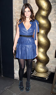Julia wears a blue leather dress in a girly cut. The bow embellished shoulder is darling!