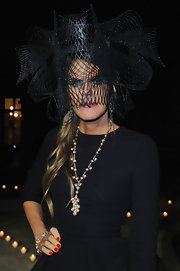 Anna Dello Russo is all about the zany headwear. For this occasion, her face was hidden behind an unexplainable net mesh creation.