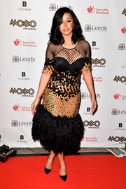 Cardi B sheathed her voluptuous figure in a black and gold Mark Fast dress, featuring a paillette midsection, a fishnet yoke and sleeves, and a feathered hem, for the MOBO Awards.