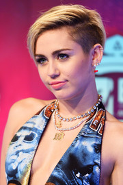 Miley Cyrus completed her accessories with a gold M pendant by Jennifer Fisher.